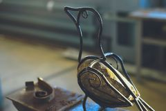 Homemade artificial bird of wire and stone body sitting on an anvil.  stock photography