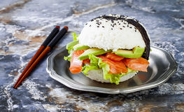 Homemade asian style gluten free sushi salmon burger. Sushi-food hybrids trend. Bright blue background with copy space. Stock Image