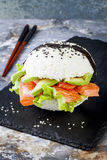 Homemade asian style gluten free sushi salmon burger. Sushi-food hybrids trend. Bright blue background with copy space. Stock Photos