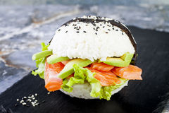 Homemade asian style gluten free sushi salmon burger. Sushi-food hybrids trend. Bright blue background with copy space. Royalty Free Stock Photos