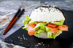 Homemade asian style gluten free sushi salmon burger. Sushi-food hybrids trend. Bright blue background with copy space. Stock Photo