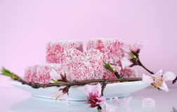 Homemade Australian style pink heart shape small lamington cakes with spring blossoms Stock Photo