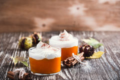 Homemade autumn dessert of pumpkin mousse with whipped cream Royalty Free Stock Photo