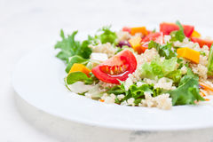 Homemade autumn healthy salad with quinoa, salad leaves, tomatoes, pumpkin and feta cheese on a white plate Royalty Free Stock Image
