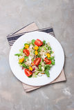 Homemade autumn healthy salad with quinoa, salad leaves, tomatoes, pumpkin and feta cheese on a white plate Royalty Free Stock Images
