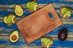Homemade avocado sandwiches on the wooden board with copy space for text. Healthy vegan diet breakfast concept. Top view royalty free stock photo