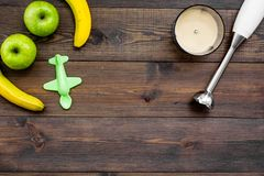 Homemade baby food. Cook puree with apple and banana with immersion blender. Dark wooden background with toy top view. Homemade baby food. Cook puree with apple Royalty Free Stock Images