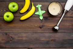Homemade baby food. Cook puree with apple and banana with immersion blender. Dark wooden background with toy top view. Homemade baby food. Cook puree with apple Royalty Free Stock Image