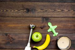 Homemade baby food. Cook puree with apple and banana with immersion blender. Dark wooden background with toy top view. Homemade baby food. Cook puree with apple Stock Images