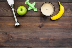 Homemade baby food. Cook puree with apple and banana with immersion blender. Dark wooden background with toy top view. Homemade baby food. Cook puree with apple Stock Photography