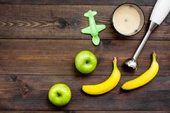 Homemade baby food. Cook puree with apple and banana with immersion blender. Dark wooden background with toy top view. Homemade baby food. Cook puree with apple Stock Photo