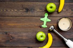 Homemade baby food. Cook puree with apple and banana with immersion blender. Dark wooden background with toy top view. Homemade baby food. Cook puree with apple Stock Image