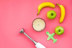 Homemade baby food. Cook puree with apple and banana with immersion blender. Pink background with toy top view space for. Homemade baby food. Cook puree with Royalty Free Stock Image