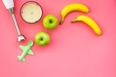 Homemade baby food. Cook puree with apple and banana with immersion blender. Pink background with toy top view space for. Homemade baby food. Cook puree with Royalty Free Stock Photos