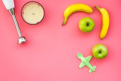 Homemade baby food. Cook puree with apple and banana with immersion blender. Pink background with toy top view space for. Homemade baby food. Cook puree with Stock Image