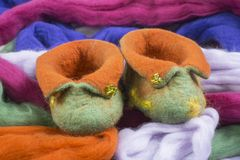 Homemade Baby slippers of thick wool felt. In the background, make a heartwarming and foot-warming gift Royalty Free Stock Image