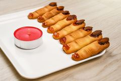 Homemade backed spooky Halloween witch finger cookies covered with sweet cherry blood royalty free stock images