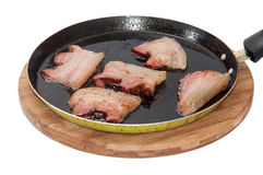 Homemade bacon in oil on a frying pan Stock Images