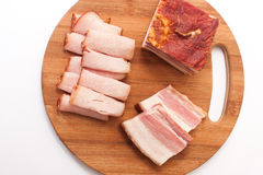 Homemade bacon and smoked ham on a kitchen board Stock Photography
