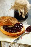 Homemade bagel with jam and tea spoon. Royalty Free Stock Images