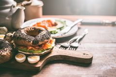 Homemade bagel sandwich topped with salmon, avocado , fresh cheese and cooked quail eggs on dark rustic wooden background. Breakfast or snack preparation royalty free stock images