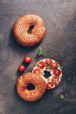 Homemade bagel with soft cheese, cherry tomatoes,basil, sesame and flax seeds on a dark rustic background. Top view, flat lay,. Copy space royalty free stock photography