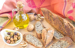 Homemade baguette, nuts, olives, olive oil on wooden board. Royalty Free Stock Photos