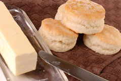 Homemade baked biscuits dripping with butter. Homemade biscuits baked and dripping with butter ready to eat laying on a brown towel with a butter dish of butter Royalty Free Stock Photography