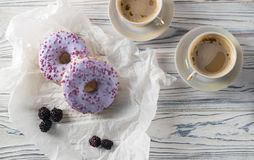 Homemade baked blackberry donuts with coffee, overhead flat lay stock photo