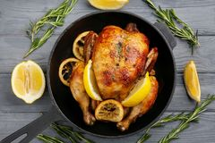 Homemade baked chicken with lemon. On wooden background royalty free stock images