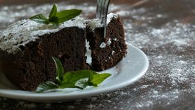 Homemade baked chocolate brownie cake muffled with powdered sugar on a white plate decorated with mint leaves. Fork. Breaks off a piece of brownie pie from the stock video footage