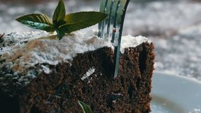 Homemade baked chocolate brownie cake muffled with powdered sugar on a white plate decorated with mint leaves. Fork. Breaks off a piece of brownie pie from the stock footage