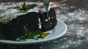 Homemade baked chocolate brownie cake muffled with powdered sugar on a white plate decorated with mint leaves. Fork. Breaks off a piece of brownie pie from the stock video