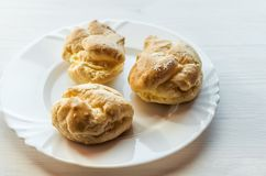 Homemade baked cream puffs on the white plate on light wooden ta Stock Images