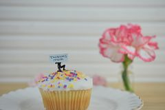 Mothers day cake and flower with a note of thankyou mum. Homemade baked cupcake with white icing and sprinkles and a thanks note held by a miniature person stock photography