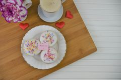 Mothers day cakes and a cup of coffee with a note of thankyou mum. Homemade baked cupcakes with white icing and sprinkles and a thank you mum note. On a wood royalty free stock image