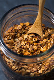 Homemade baked granola in a glass jar, vertical closeup Stock Image