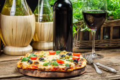 Homemade baked pizza served with wine Royalty Free Stock Image