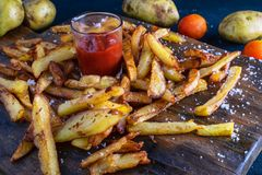 Homemade Baked Potato Fries with ketchup on wooden back ground royalty free stock image
