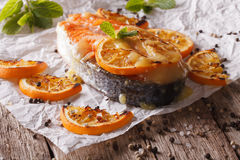 Homemade baked salmon steak with oranges on baking paper. Horizo Royalty Free Stock Photography