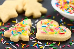 Homemade Baked Sugar Cookies with Colorful Sprinkles. Homemade baked sugar cookies for Christmas with icing and colorful sprinkles on the top Selective Focus stock photos