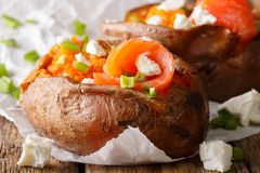 Homemade baked sweet potato stuffed with salmon and green onions. Close-up on parchment on the table. horizontal Stock Photos