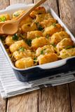 Homemade Baked Tater Tots with cheese, meat and greens close up. In a baking dish on the table. vertical Royalty Free Stock Photography