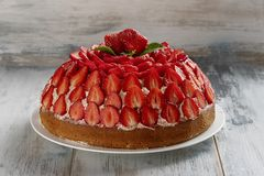 Homemade bakery concept. Strawberry cake with vanilla cream decorated with fresh  strawberries and mint on a wooden background. Selective focus. Close up royalty free stock image