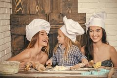 Homemade baking and cooking. Child and women kneading dough. Happy family and childhood concept. Boy and girls in chef hats. Brother and sisters at table using Stock Images