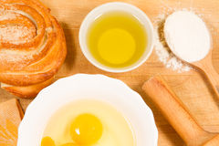 Homemade baking. Fresh rosy bun, cooking rolling pin, spoon of flour, broken eggs, sunflower oil, chopping Board Royalty Free Stock Photo