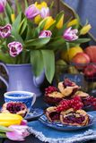 Homemade baking. fruitcake with red berries. tasty breakfast. Flowers and apples. fresh tulips . stock photography
