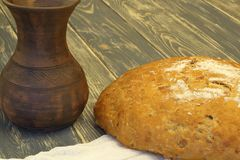 Homemade delicious soft yeast rye bread on a white cloth and clay jug on dark natural wooden background stock images