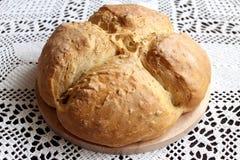 Homemade baking. Splendid ruddy white flour bread on a wooden stand on the background of handmade handmade cotton napkin stock image