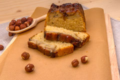 Homemade banana cake on baking brown paper. Slices of homemade banana cake, wooden spoon with hazelnuts on a baking brown paper on a wooden board, close-up front Stock Image